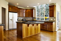 A brightly lit kitchen with wood floors and cabinets.