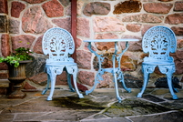 A bistro set on a patio painted baby blue.