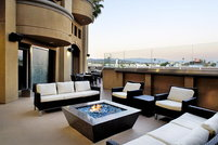 A fire pit on the patio of a luxurious home.