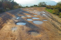 A dirt road with several potholes filled with water.