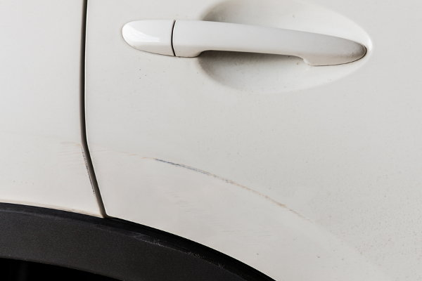 A close-up of a white car with a scratch by the handle.