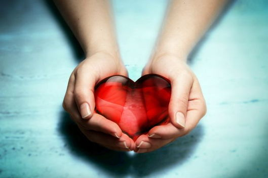 pair of hands cupped and holding a crystal heart