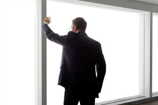 man wearing a suit looks out the window