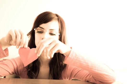 woman looking sad holding paper heart