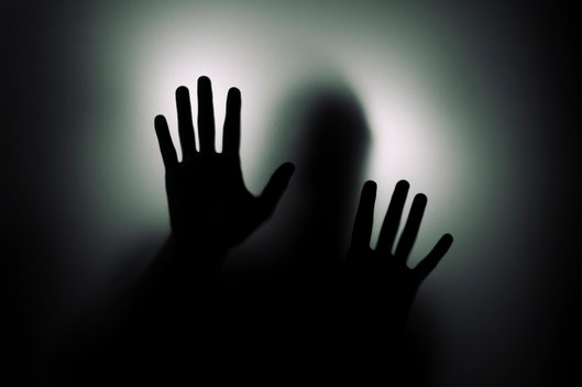 man in shadows with hands in the air