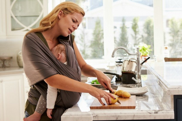 Mother carries child on sling while preparing dinner and talking on the phone
