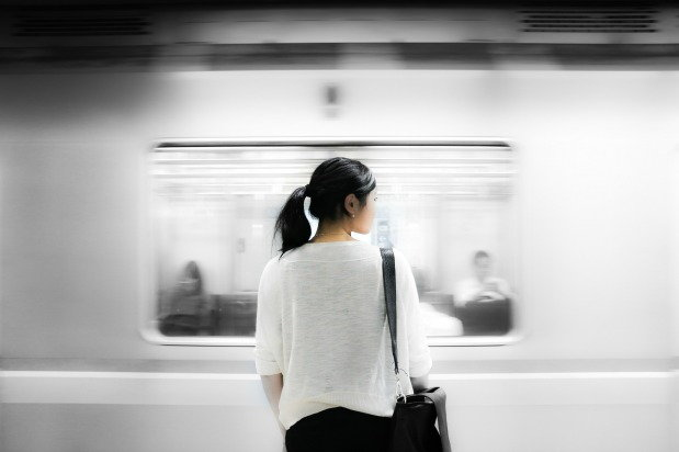 Woman stands still as the train passes her by