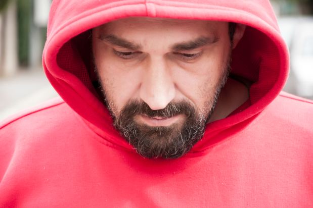 Man in red hoodie thinking about recovery