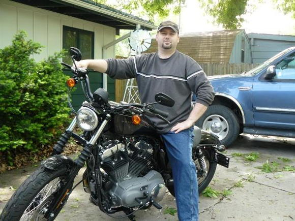 Me on the Nightster before any mods.  Hell, I think it had like 7 miles on it when I took this picture.  There's a bunch of crap on the ground from a real bad storm we had the night before.