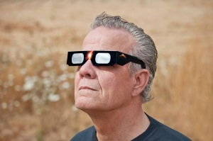 man viewing eclipse with safety glasses