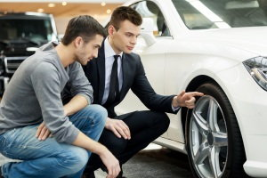 man and salesperson look at car at dealership