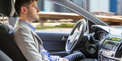 man sitting in self-driving car, autonomous car