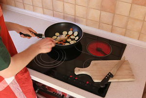 Someone cooking food on an induction cooktop.