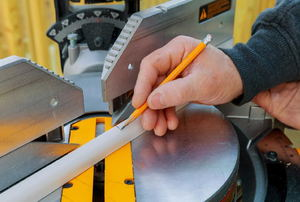 Man marking a cut point on a  piece of quarter round molding.