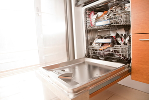 A dishwasher with a door hanging open in a bright room.