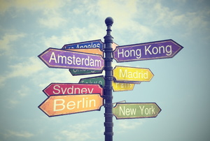 A colorful sign with directionals for different countries against a blue sky.