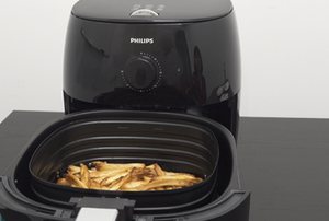 A Philips Airfryer with fries in the basket.