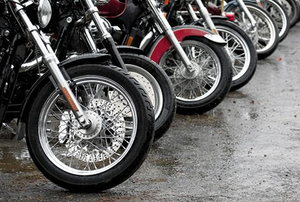The front wheels of a line of motorcycles.