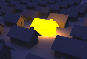 A row of dark houses with one glowing yellow.