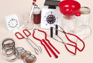 A collection of supplies for canning, including tongs and jar lids.