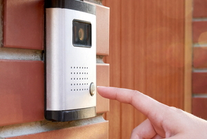 A finger ringing a doorbell that has a camera