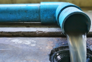 pvc drain pipe flowing water into a drain