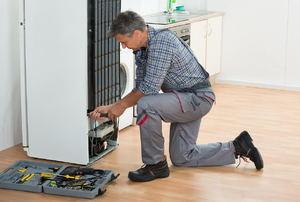 A man works on a fridge.