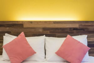 A rustic wood headboard with white and pink pillows.