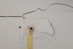 A crack and hole in drywall that needs to be repaired.