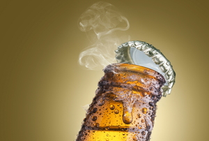 The top pops off of a cold bottle of beer.