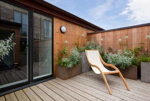 furnished outdoor deck with plants and a sliding glass door