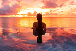 woman in infinity pool watching sunset