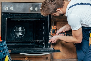A man works on an oven.