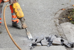 person in protective gear using a jackhammer to remove a concrete walkway