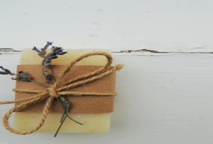 A piece of homemade organic goat milk soap tied with a piece of lavender and twine.