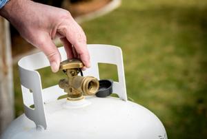 hand twisting the control valve on a propane tank