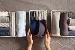 organizing folded clothes in canvas bins