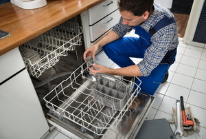 A man removing the drain from a dishwasher.
