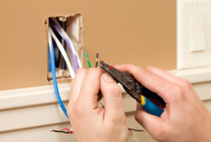 The green, black, and red wires in 220v wiring are pulled from the outlet to be worked on.