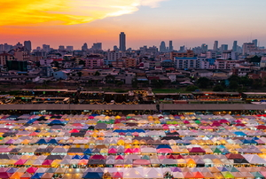 a flea market with colorful tents in a city at sunset