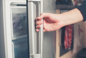 A person opening a refrigerator door.