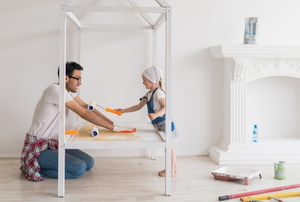 Two people paint a home.