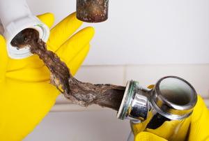 gloved hands unclogging sink drain