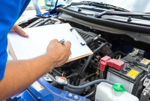 A man look at an engine while writing on a clipboard.