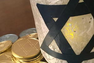 A Mason jar decorated with a Star of David surrounded by Hanukkah-themed candy.