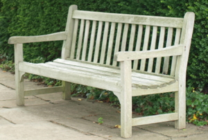A wooden bench on a paver patio next to a hedge.