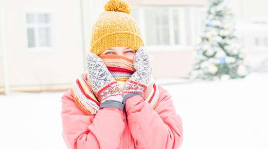 Image of a girl in the snow wearing a scarf, mittens, and a beanie.