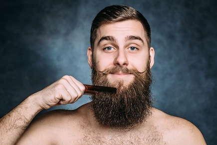 Image of man combing his long beard.