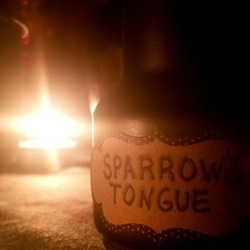 bottle labeled sparrow's tongue with candles lit
