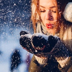 girl blowing on handful of snow